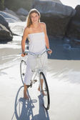 Blonde standing with bike on beach — Foto Stock