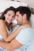 Attractive couple cuddling on bed — Stock Photo