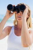 Blonde looking through binoculars — Stok fotoğraf