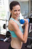 Fit brunette lifting dumbbells — Stock Photo