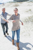 Couple playing chasing on the beach — Stock Photo