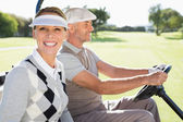 Happy golfing couple driving in their buggy — Stock Photo