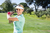 Female golfer taking a shot — Stock Photo