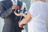 Estate agent giving house key to buyer — Stockfoto