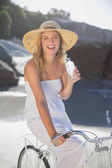 Blonde on bike holding water bottle at beach — Stock Photo