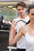 Woman lifting barbell with her trainer — Stock Photo