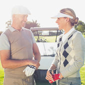 Golfing couple chatting with golf buggy behind — Stock Photo