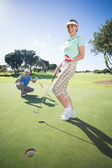 Golfing couple cheering on the putting green — Stock Photo