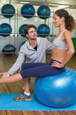 Trainer watching his client lift leg on exercise ball — ストック写真