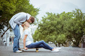 Blonde on skateboard with boyfriend kissing forehead — Stock Photo