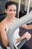 Brunette using weights machine for arms — Stock Photo