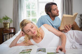 Couple on bed reading books — Foto de Stock
