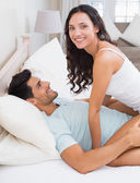 Brunette straddling boyfriend on bed — Stock Photo