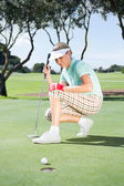 Golfer watching her ball on putting green — Stockfoto