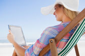 Woman in deck chair using tablet — ストック写真