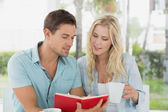 Hip couple having coffee and reading book — Stock Photo