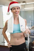 Fit brunette in santa hat holding bottle — Стоковое фото
