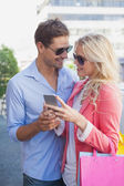 Stylish couple looking at smartphone — Foto de Stock