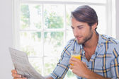 Smiling man having orange juice — Stockfoto