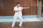 Handsome man in white doing tai chi — Stock Photo