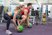 Bodybuilding man and woman lifting balls — Stock Photo