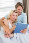 Couple on couch using tablet — Stockfoto