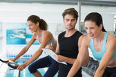 Fit women in a spin class with trainer taking notes — Stock fotografie