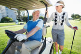 Golfing couple setting out for day on buggy — Stok fotoğraf
