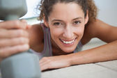 Fit woman smiling holding dumbbell — Stock Photo