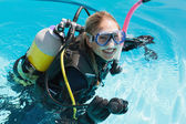 Smiling woman on scuba training in swimming pool — Stock Photo