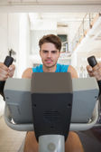 Focused fit man on the exercise bike — Stock Photo