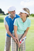 Golfing couple putting ball together — Стоковое фото