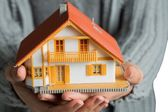 Hands showing a miniature model home — Foto Stock