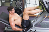 Bodybuilder working with weight machine — Stock Photo
