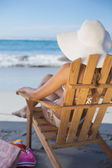 Woman in straw hat relaxing in deck chair — Stock Photo