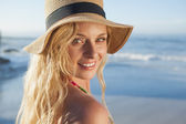 Blonde in straw hat smiling on beach — Stockfoto