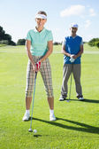 Golfer teeing off for the day watched by partner — Stock Photo
