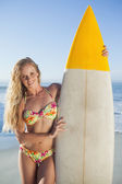 Blonde surfer in bikini holding her board — Stock Photo