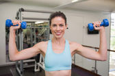 Woman lifting blue dumbbells — Foto Stock
