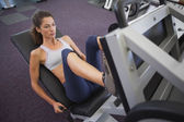 Woman using weights machine for legs — Stock Photo
