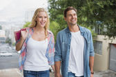 Couple on shopping trip walking uphill — Stockfoto