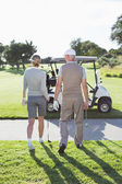 Golfing couple walking towards the buggy — Stock Photo