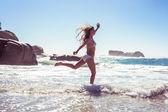 Woman in bikini skipping on the beach — Stock Photo