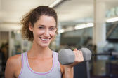 Fit woman smiling lifting dumbbell — Stock Photo