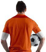 Fotbalista v oranžové držení míče — Stock fotografie