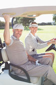 Golfing couple smiling in their buggy — Stock Photo