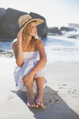 Blonde in sundress sitting on the beach — Stok fotoğraf