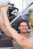 Personal trainer coaching bodybuilder using weight machine — Foto Stock