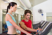Trainer helping his client set treadmill speed — Photo