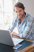 Smiling man using laptop — Stock Photo